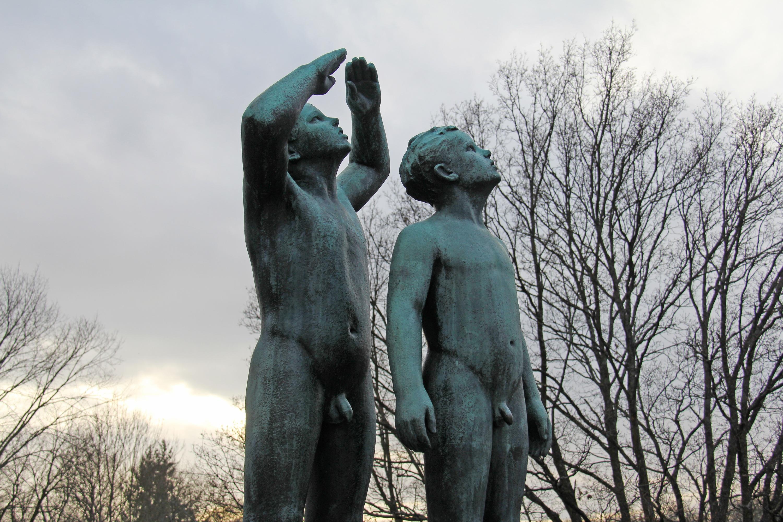 Dos niños desnudos de bronce miran al cielo