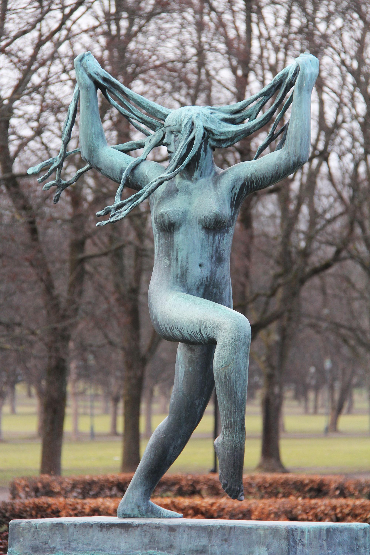 Una jóven desnuda de bronce corre mientras juega con sus trenzas