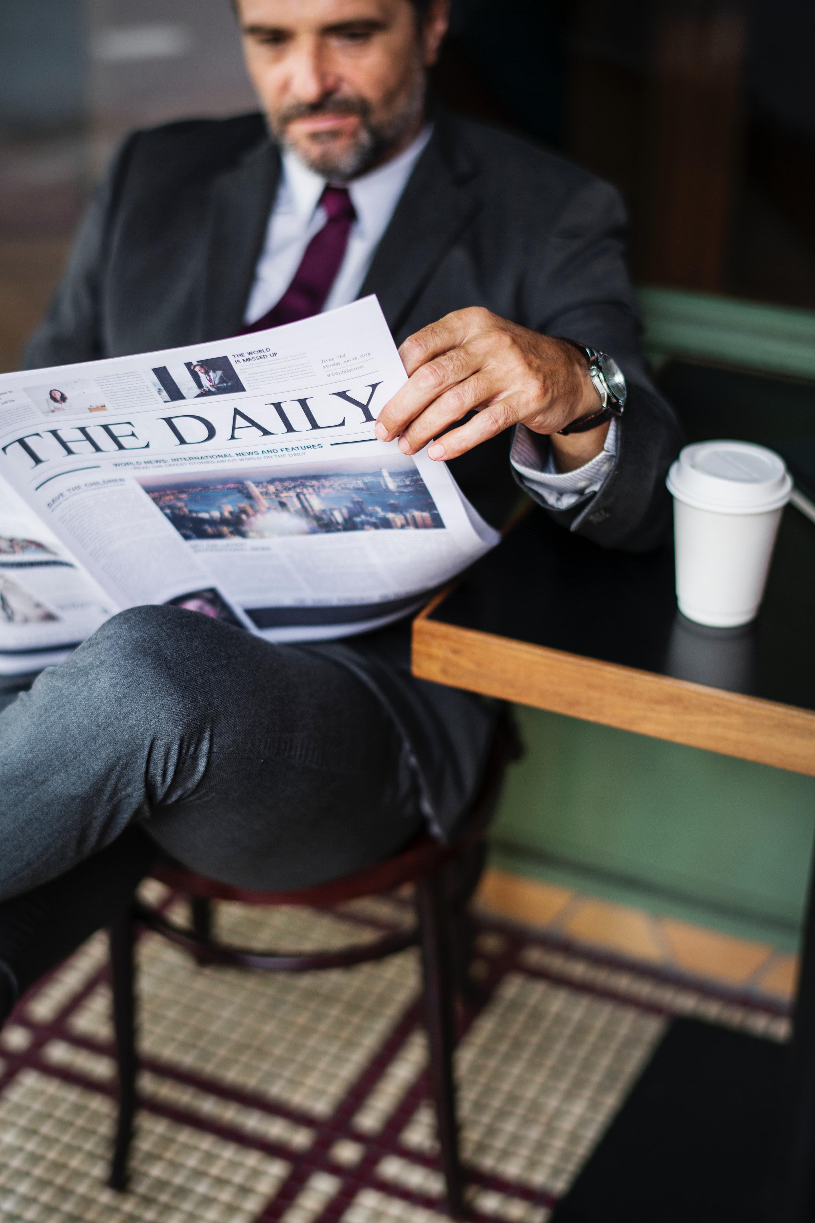Человек читает газету фото