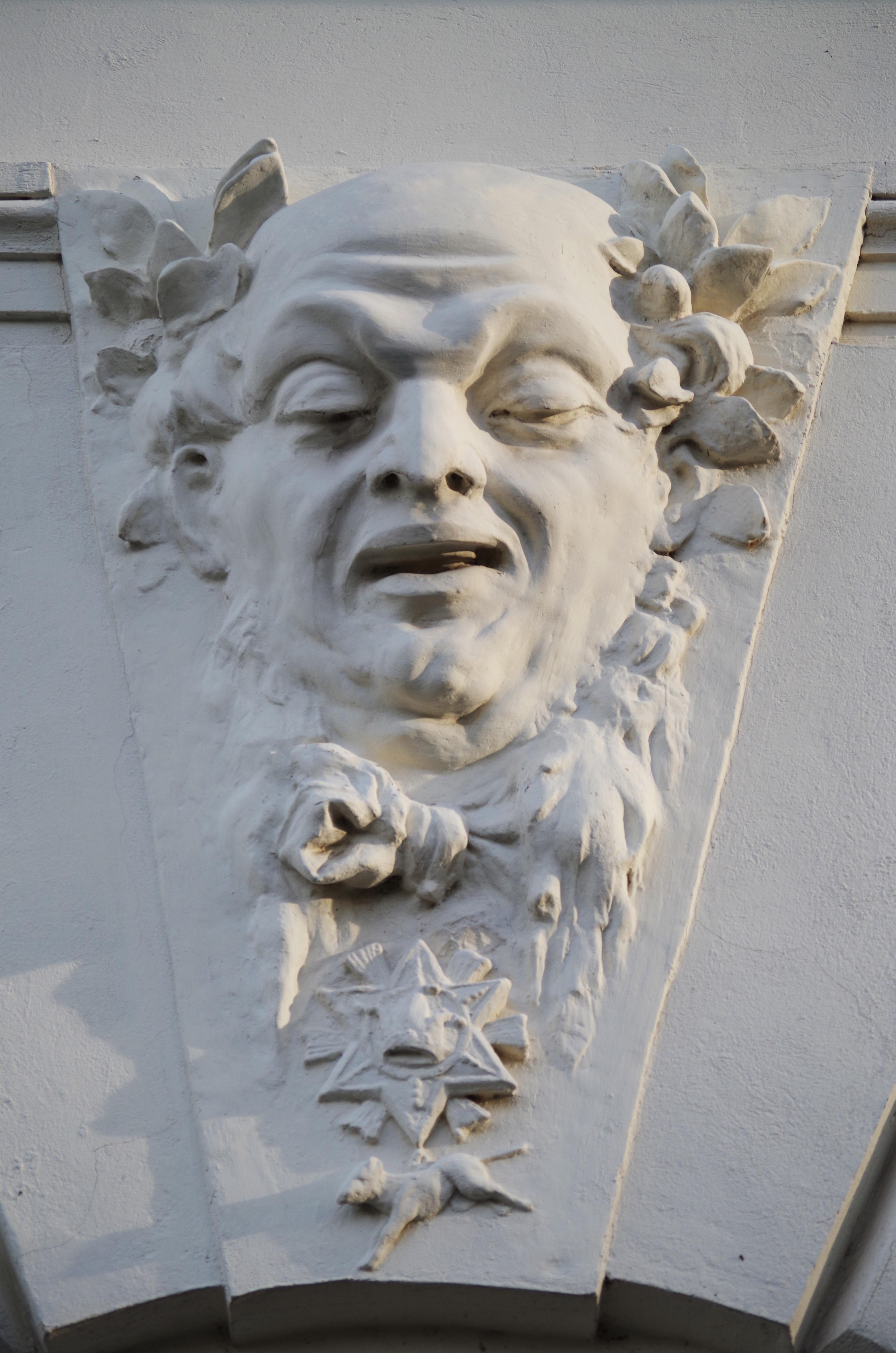 фото голова в стене скульптура даже