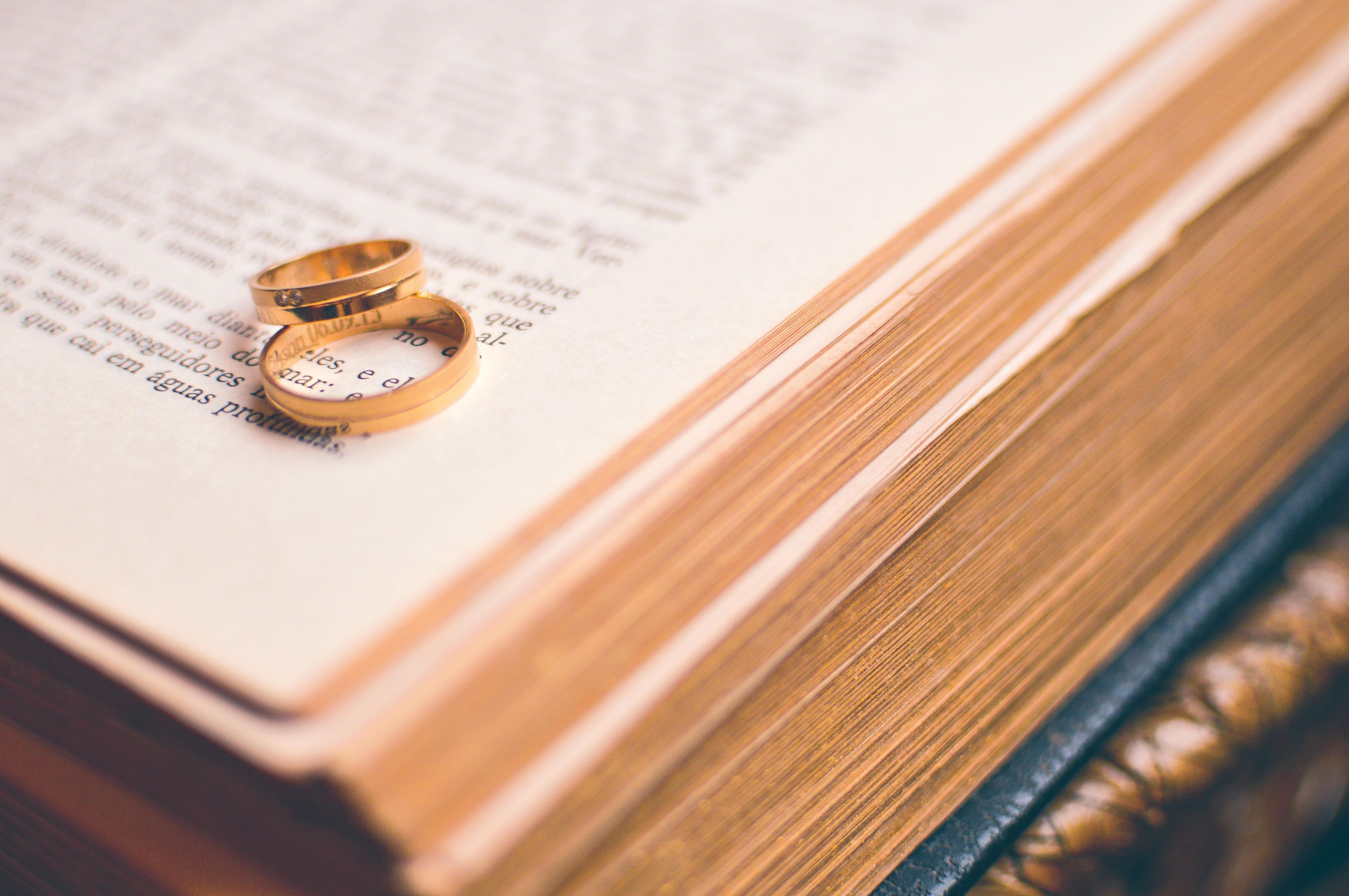 Matrimonio Y Biblia : Los anillos de boda sobre una biblia abierta en un versículo del
